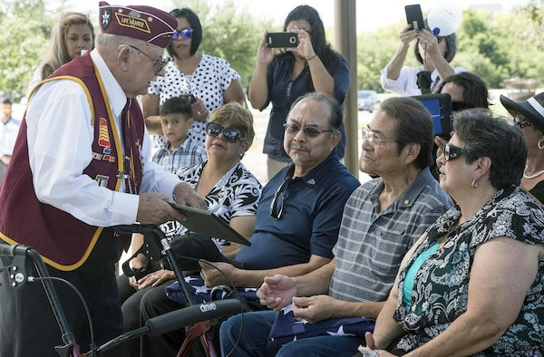 Oscar Cortez (left), a former Korean War POW who served in the same unit with Army Cpl. Frank Sandoval, presents a framed photo of the unit he and Sandoval served in while they were in action to Sandoval's sons, Frank Jr. and Alejandro, July 11. Cortez, 85, said the photo was taken three to four days before their unit was captured.