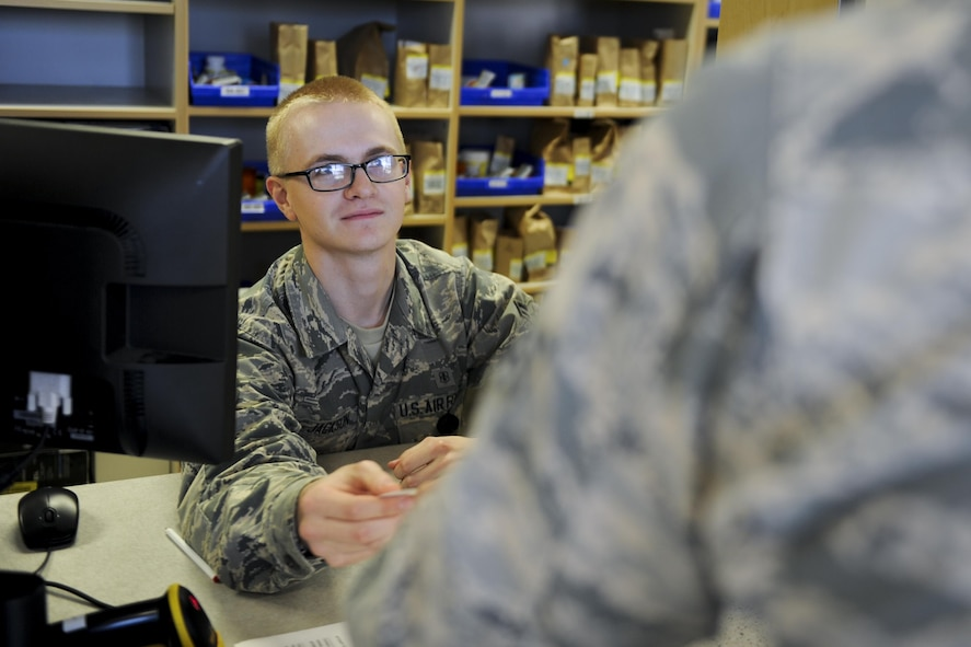 Airman 1st Class Gavin Jackson, a pharmacy technician with the 1st Special Operations Medical Group, gives a patient a third party collection verification card at Hurlburt Field, Fla., July 11, 2017. TPC verification cards verify a patient's updated medical insurance information to ensure Hurlburt's Air Commandos are eligible for prescription medications. (U.S. Air Force photo by Airman 1st Class Dennis Spain)