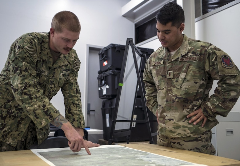 A U.S. Navy Helicopter Sea Combat Squadron-85 intelligence analyst points out locations on a map of Central Queensland in Australia to a U.S. Air Force 1st Special Operations Squadron intelligence officer, as the analysts build the intelligence picture for the warfighting scenario of Talisman Saber 2017, July 10, 2017 at Rockhampton, Australia. Aside from service components working with the Australian military, the exercise also provided an opportunity for U.S. forces to integrate intelligence systems and share tactics, trainings and procedures with other U.S. services.
