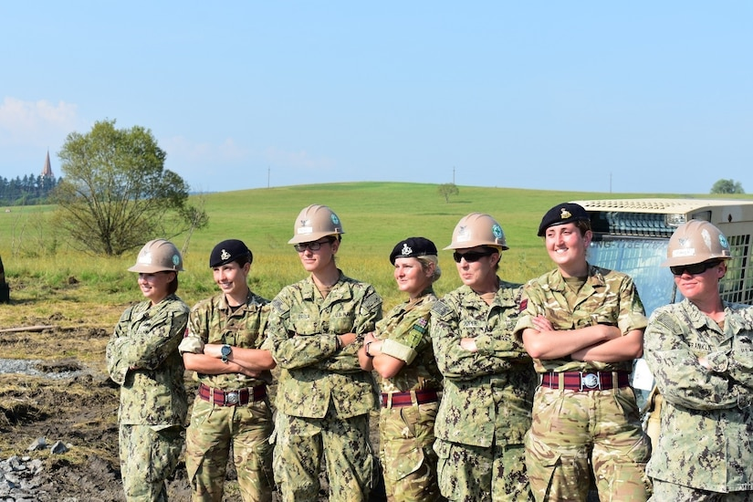Sappers from the British Army Reserve's Royal Monmouthshire Royal Engineers (Militia) and Seabees from the Naval Mobile Construction Battalion 1 pose in front of engineering equipment at the Joint National Training Center, Cincu, Romania, for International Women in Engineering Day, June 23, 2017. The service members were participating in exercise Resolute Castle. Army photo by Capt. Colin Cutler