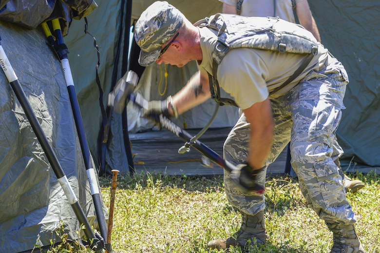 U.S. Air Force Staff Sgt. Robert Joyce, 644th Combat Communications Squadron cyber transport technician, constructs a tent during exercise Dragon Forge June 12, 2017. Day one of the training exercise started with the 644th CBCS team being tasked with setting up a forward operating base with concertina wire around the perimeter. (U.S. Air Force photo by Airman 1st Class Christopher Quail)