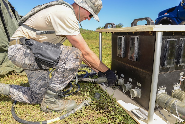 U.S. Air Force Staff Sgt. Zachary Bieranowski, 644th Combat Communications Squadron power production technician, connects generators that power the unit's equipment during exercise Dragon Forge June 12, 2017, at Andersen South, Guam. Day one of the training exercise started with the 644th CBCS team being tasked with setting up a forward operating base with concertina wire around the perimeter. (U.S. Air Force photo by Airman 1st Class Christopher Quail)