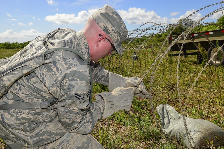 U.S. Air Force Airman 1st Class Kevin Hull, 644th Combat Communications Squadron radio frequency technician, places concertina wire around a forward operating base during exercise Dragon Forge June 12, 2017, at Andersen South, Guam. Day one of the training exercise started with the 644th CBCS team being tasked with setting up a forward operating base. (U.S. Air Force photo by Airman 1st Class Christopher Quail)