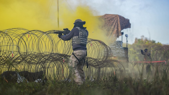 A U.S. Airman, acting as an opposing force, fires paintball rounds at 644th Communications Squadron Airmen during exercise Dragon Forge June 15, 2017, at Andersen South, Guam. Opposing forces repeatedly attacked the base throughout the day prior to an all-out final attack from all sides with the goal of overrunning the base. (U.S. Air Force photo by Airman 1st Class Christopher Quail)