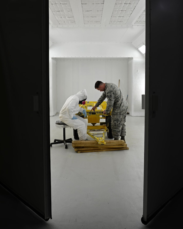 Senior Airman Jeremy Washington, 374th Maintenance Squadron aircraft structural journeyman, deployed from Yokota Air Base, Japan, (left) and U.S. Air Force Staff Sgt. Brendan McCormick, 36th Maintenance Squadron corrosion control NCO in charge, inspect a weapons trailer June 27, 2017, at Andersen Air Force Base, Guam. Airmen began work in Andersen's new temporary corrosion control facility June 5th. (U.S. Air Force photo by Senior Airman Alexa Ann Henderson)