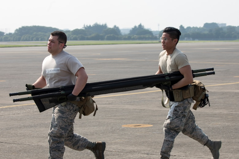 Senior Airman Jonathan Rodriguez and SrA Richson Bacay, both 374th Medical Operations Squadron aerospace medical technicians, carry a stretcher during a major accident response exercise at Yokota Air Base, Japan, July 10, 2017. The training exercise simulated a C-130 Hercules accident with varying levels of injuries. Personnel conducted the drill to ensure they are ready for any aircraft emergency. (U.S. Air Force photo by Yasuo Osakabe)