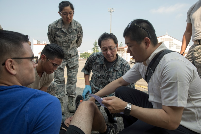 First responders from the Kyorin University Hospital, Japan Air Self-Defense Force Air Defense Command and U.S. Air Force Senior Airman Richson Bacay, 374th Medical Operations Squadron aerospace medical technician, work together to aid a simulated aircraft accident victim during a major accident response exercise (MARE), at Yokota Air Base, Japan, July 10, 2017. During a MARE all simulated medical injuries and victims are treated as real by firefighters and medical airmen adding the importance of urgency to the training. (U.S. Air Force photo by Yasuo Osakabe)