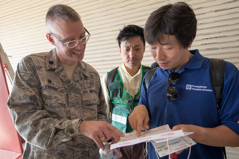 Lt. Col. Graham Warden, 374th Medical Operations Squadron commander, explains an exercise inject card to emergency response personnel from the Kyorin University Hospital during a major accident response exercise at Yokota Air Base, Japan, July 12, 2017. This is the first time Japanese emergency response personnel from the Kyorin University Hospital and Japan Air Self-Defense Force from the Air Defense Command participated in a MARE ensuring they are ready for any aircraft emergency. (U.S. Air Force photo by Yasuo Osakabe)