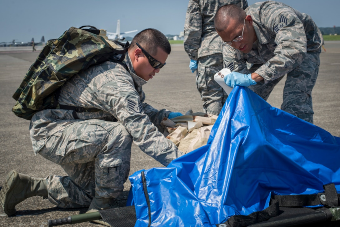 Staff Sgt. Johnny Liu, left, and Staff Sgt. Kenny Bradley, 374th Force Support Squadron search and recovery team members, process simulated body parts found scattered during a major accident response exercise, June 10, 2017, at Yokota Air Base, Japan. The exercise is designed to test a wing's ability to respond to a variety of different events that could be disastrous to the installation and negatively impact the mission. (U.S. Air Force photo by Airman 1st Class Juan Torres)