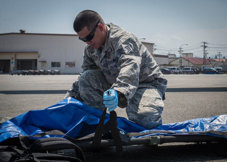 Staff Sgt. Johnny Liu, 374th Force Support Squadron search and recovery team member, prepares a litter for use during a major accident response exercise, June 10, 2017, at Yokota Air Base, Japan. The training helps Airmen respond to a crisis situation they may face during a large casualty accident. (U.S. Air Force photo by Airman 1st Class Juan Torres)
