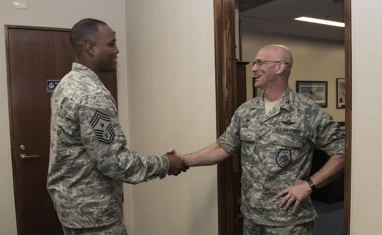 U.S. Air Force Chief Master Sgt. Anthony Johnson, left, the Pacific Air Forces' command chief, shakes hands with Col. R. Scott Jobe, the 35th Fighter Wing commander, right, during a visit at Misawa AIr Base, Japan, July 11, 2017. During his tour, Johnson met with various shops and organizations while sharing his goals for improving PACAF's enlisted force so they can work at their optimal level. (U.S. Air Force photo by Airman 1st Class Sadie Colbert)