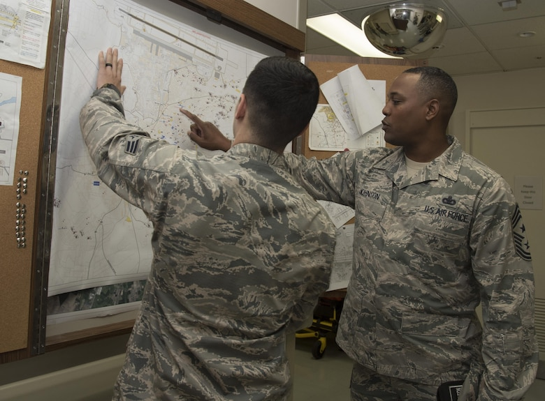 U.S. Air Force Senior Airman Dylan Gorr, left, a 35th Medical Operations Squadron aerospace medical service technician, looks at a map of Misawa City, Japan, with Chief Master Sgt. Anthony Johnson, the Pacific Air Forces' command chief, during his tour at Misawa Air Base, Japan, July 11, 2017. During the visit, Airmen explained their current capabilities as well as the challenges they face in their career. (U.S. Air Force photo by Airman 1st Class Sadie Colbert)