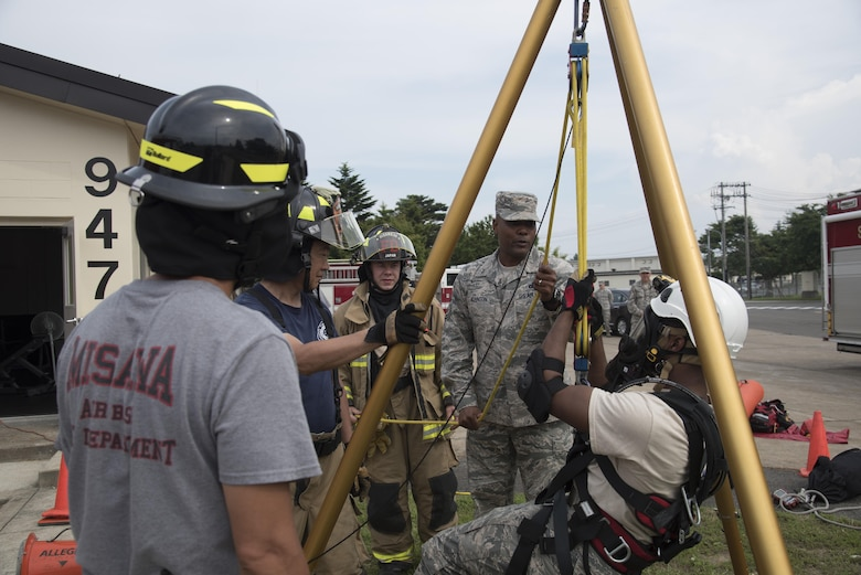 U.S. Air Force Chief Master Sgt. Anthony Johnson, the Pacific Air Forces' command chief, watches 35th Civil Engineer Squadron firefighters demonstrate entering a confined space using a tripod, at Misawa Air Base, Japan, July 11, 2017. Johnson, once a security forces troop, now oversees more than 40,000 enlisted personnel in his position and advises the PACAF commander on all matters affecting the readiness, training, professional development and effective utilization of assigned enlisted members. (U.S. Air Force photo by Airman 1st Class Sadie Colbert)