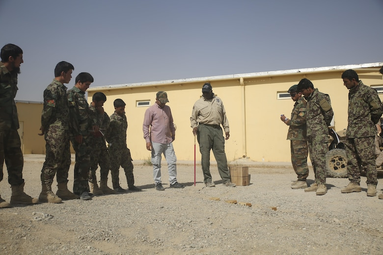 A counter improvised explosive device instructor teaches proper route clearance procedures using a terrain model to Afghan National Army soldiers with 215th Corps at Camp Shorabak, Afghanistan, July 13, 2017. Several U.S. Marine advisors with Task Force Southwest and instructors began a route clearance course July 8, which is designed to help improve the mobility of ANA forces in Helmand Province. (U.S. Marine Corps photo by Sgt. Lucas Hopkins)