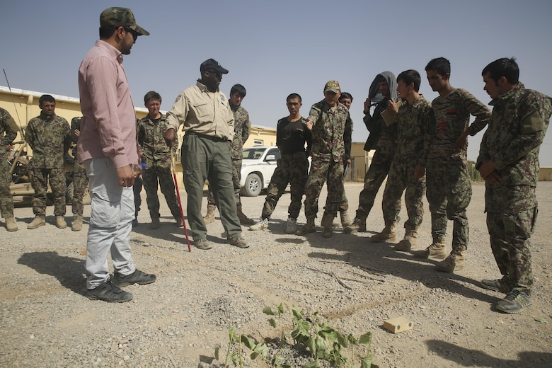 An Afghan National Army soldier with 215th Corps indicates a possible location for an improvised explosive device using a terrain model at Camp Shorabak, Afghanistan, July 13, 2017. Approximately 70 engineer soldiers with various units from the 215th Corps recently began a route clearance course, an eight-week training cycle designed to enhance their counter IED skills and help promote maneuverability throughout the region. (U.S. Marine Corps photo by Sgt. Lucas Hopkins)