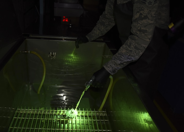 Senior Airman Brett Gyurnek , 437th Maintenance Squadron Non-Destructive Inspection technician, covers a core reverser gear with fluorescent penetrant during a deficiency inspection at Joint base Charleston, S.C. July 10, 2017. Fluorescent penetrant testing is a reliable way to illuminate fractures on the surface of damaged aircraft parts. It is done by submerging the part in a fluorescent liquid and allowing the dye to penetrate into any cracks. The liquid is then rinsed off and placed in a developing agent which makes the fluorescent liquid illuminate brighter under an ultraviolet light. The part is then placed under an ultraviolet light and, if cracks are present, they will light up and make the deficiency more visible.