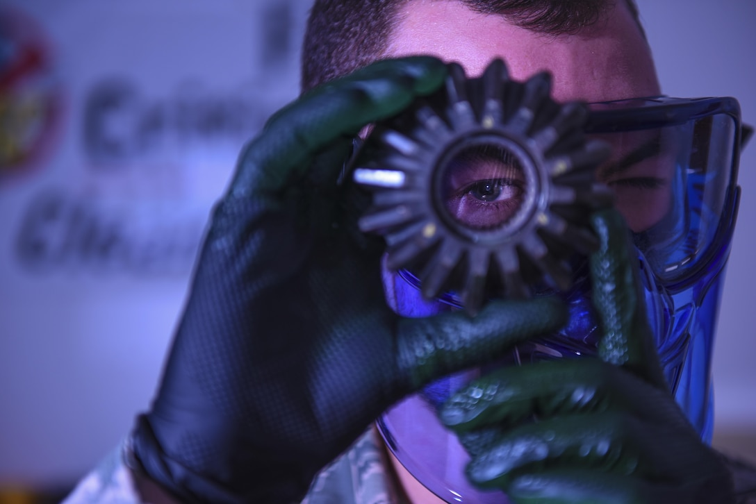 Senior Airman Brett Gyurnek, 437th Maintenance Squadron Non-Destructive Inspection technician, looks through a core reverser gear while performing a fluorescent penetrant test at Joint Base Charleston, S.C. July10, 2017. The NDI shop is able to test the largest and smallest pieces of an aircraft. Once a deficiency is found, it is relayed to the aircraft structural maintenance unit for repair. If a crew chief or a member of the aircrew identifies a potential issue, NDI Airmen perform diagnostic procedures to determine the extent of the damage.