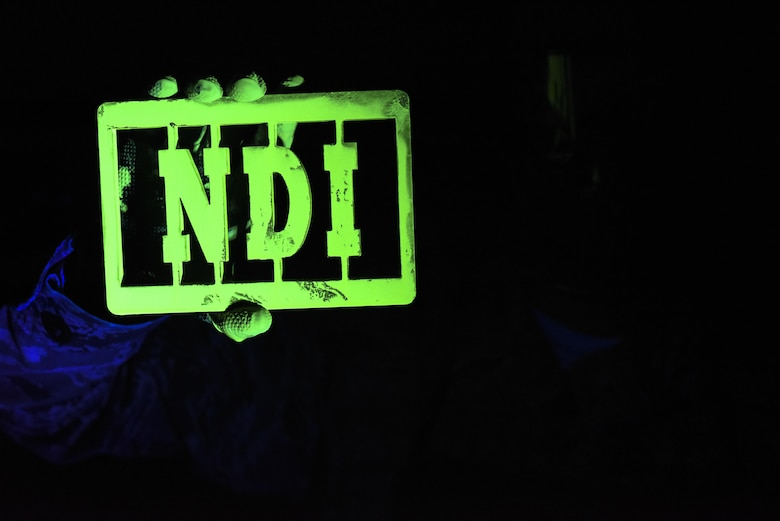 Senior Airman Brett Gyurnek, 437th Maintenance Squadron Non-Destructive Inspection technician, holds up a piece of inscribed metal covered in fluorescent penetrant under an ultraviolet light at Joint Base Charleston, S.C. July 11, 2017. The Airmen of the 437th MXS NDI shop use diagnostic procedures to determine if aircraft parts are unsafe or compromised.