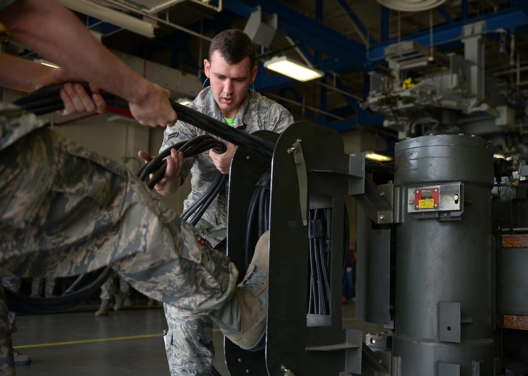 Senior Airman Luke Ryan, 705th Munitions Squadron special purpose vehicle operator and Airman 1st Class Jacob Lowe, 705th MUNS team member roll up a common strategic rotery launcher electrical cord Challenge at Minot Air Force Base, N.D., June 30, 2017. The Airmen were part of a team that participated in a mate-and-tow maneuver during Global Strike Challenge 2017. (U.S. Air Force photo by Staff Sgt. Chad Trujillo)