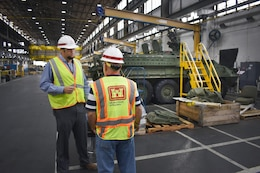 Chad McLeod, area engineer, South Alabama Area Office, Mobile District; at left, speaks to John McLain, resident engineer; in the 41,000 square feet of the facility where metal cleaning, finishing and painting takes place for many Army vehicles. Mobile District recently completed a $9.5 million modernization of the building.