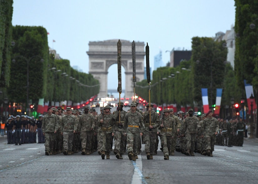 Almost 200 U.S. soldiers, sailors, Marines and airmen assigned to units in Europe and the 1st Infantry Division based at Fort Riley, Kansas, march from the Arc de Triomphe to the Place de la Concorde during a July 12 rehearsal for the military parade on Bastille Day to be held in Paris, July 14, 2017. Navy photo by Chief Petty Officier Michael McNabb