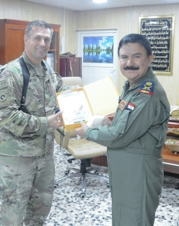 CAMP TAJI, Iraq - U.S Army Col. Mark Beckler, 29th Combat Aviation Brigade commander, is presented with a plaque by Iraqi Maj. Gen. Khalid Al Shimry, the new aviation base commander of Camp Taji Military Complex, at Camp Taji Military Complex, Iraq, July 6, 2017. The 29th CAB is an Army National Guard unit that is currently deployed in support of Combined Joint Task Force - Operation Inherent Resolve. CJTF-OIR is the global Coalition to defeat ISIS in Syria and Iraq.  (U.S. Army Photo by Capt. Stephen James)