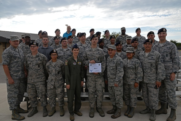"""XLer of the week"" winner, U.S. Air Force SrA Isaac L. W. Saul accepts his award with members of the 47th Security Forces Squadron, along with Col. Michelle Pryor, 47th Flying Training Wing vice commander, and Chief Master Sgt. George Richey, 47th FTW command chief, at Laughlin Air Force Base, Tx., July 12, 2017. The ""XLer"" award, presented by wing leadership, is given to those who consistently make outstanding contributions to their unit, and Laughlin mission."