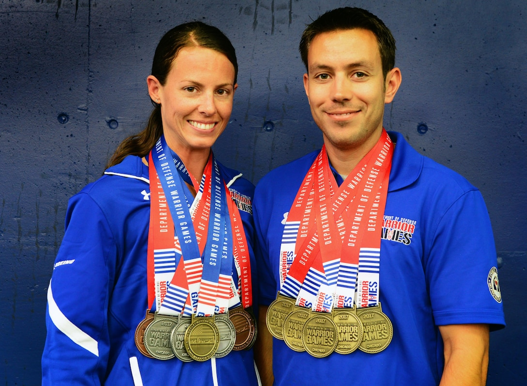 U.S. Air Force Master Sgts. Linn Knight and Kenneth Guinn, explosive ordnance disposal specialists assigned to Tyndall Air Force Base, Fla., pose for a photo with their official Warrior Games medals July 8, 2017 at the University of Illinois at Chicago, Chicago, Ill. The commonalities between the lives of these two warriors are uncanny and extensive; from growing up in the same city and joining the Air Force in the same year, to a traumatic run-in with an IED on the same day. While sharing similar career assignments and progression, Guinn and Knight have forged a friendship built upon on a life of shared experiences. (U.S. Air Force photo by Staff Sgt. Chip Pons)