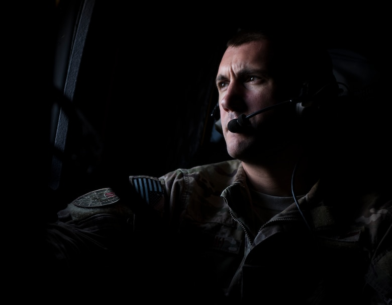Staff Sgt. Jeremy Wolski, a loadmaster with the 15th Special Operation Squadron, looks out the paratroop door window of an MC-130H Combat Talon II while flying to Total Force Exercise 17-3, over Louisville, Ky., July 8, 2017. The Total Force Exercise enhances 1st Special Operations Wing Air Commandos' interoperability with other units and services. (U.S. Air Force photo by Tech. Sgt. Jeffrey Curtin)