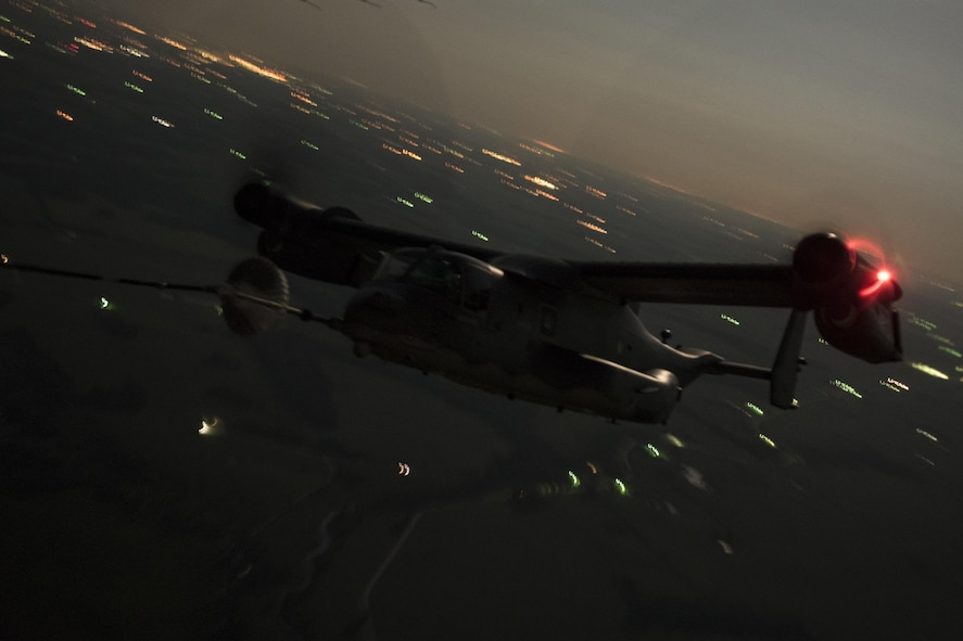 An 8th Special Operations Squadron CV-22 Osprey tiltrotor aircraft receives fuel from a 15th SOS MC-130H Combat Talon II during a total force exercise night-time aerial refueling mission over Louisville, KY., July 9, 2017. Units from the 1st Special Operations Wing conduct quarterly exercises with other units and services to increase consistency in tactics and procedures, ensuring their global readiness. (U.S. Air Force photo by Tech. Sgt. Jeffrey Curtin)