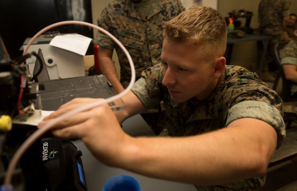 A Marine calibrates a three-dimensional printer during the 3-D Printing Training Course at Marine Corps Base Camp Lejeune, North Carolina. Marines have been embracing 3-D printing for several years now, and there are more than 40 units using 3-D printers in the field to build drones, buildings, vehicles and other items out of various materials. (U.S. Marine Corps photo by Sgt. Ian Leones) [High-resolution photo]