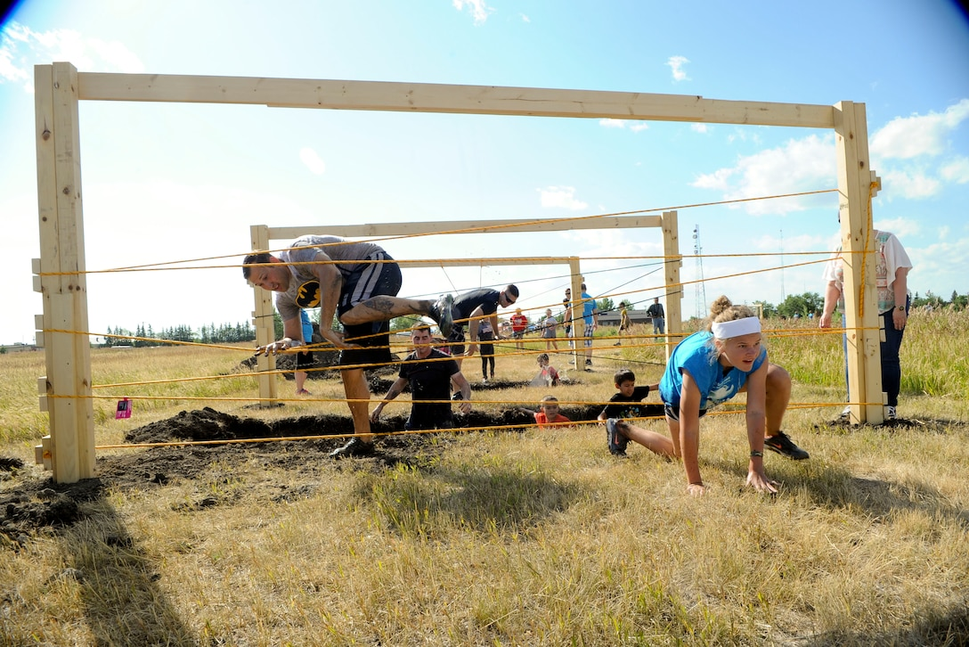 Airmen and their families make their way through an obstacle during the 2017 Mud Like You Mean It race at Minot Air Force Base, N.D., July 7, 2017. The event consisted of various obstacles that challenged their ability to crawl, climb, run and slide through mud and water. (U.S. Air Force photo by Senior Airman Sahara L. Fales)