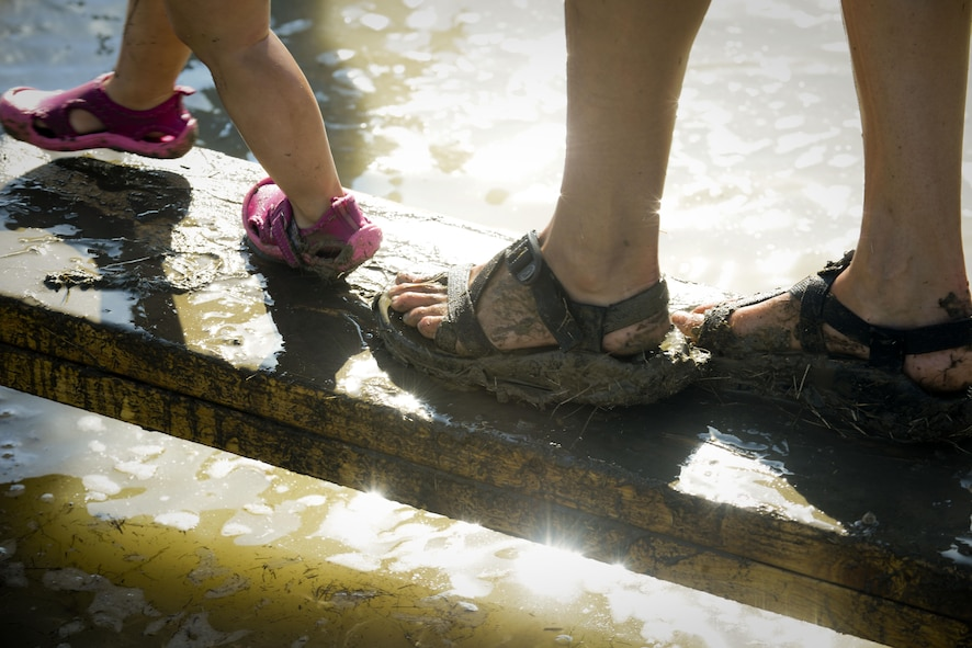 A child and their parent walk across a plank during the 2017 Mud Like You Mean It race at Minot Air Force Base, N.D., July 7, 2017. The event consisted of various obstacles that challenged their ability to crawl, climb, run and slide through mud and water. (U.S. Air Force photo by Senior Airman Sahara L. Fales)