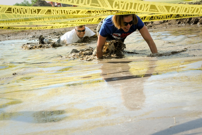 Col. William Barrington, 91st Maintenance Group commander, and Col. Catherine Barrington, 91st Operations Group commander, crawl through mud at Minot Air Force Base, N.D., July 7, 2017. The low-crawl was one of many obstacles that tested participants' balance, endurance and strength. (U.S. Air Force photo by Senior Airman Sahara L. Fales)