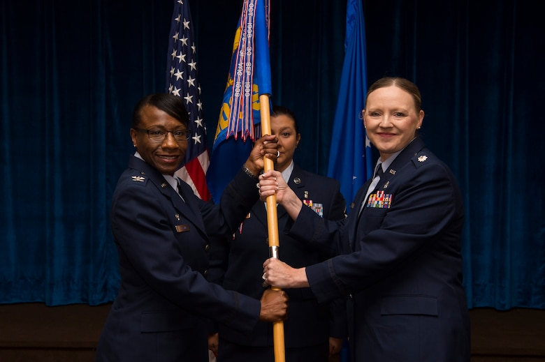 Col. Cherron Galluzzo, 90th Medical Group commander, passes the guidon to Lt. Col. Angela Lacek, 90th Medical Operations Squadron commander, during the 90th MDOS change of command ceremony at F.E. Warren Air Force Base, Wyo., July 13, 2017. The ceremony signified the transition of command from Lt. Col. John Modra. (U.S. Air Force photo by Staff Sgt. Christopher Ruano)
