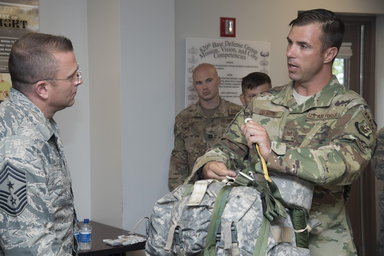 Tech. Sgt. Joseph Ostrum, 823d Base Defense Squadron jumpmaster, explains the functionality and differences between two parachute designs to Chief Master Sgt. David Wade, 9th Air Force command chief, during his visit, July 11, 2017, at Moody Air Force Base, Ga. Wade visited the 93d Air Ground Operations Wing and its units at Moody to learn about the units' missions and capabilities. (U.S. Air Force photo by Staff Sgt. Eric Summers Jr.)