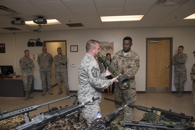 Staff Sgt. Ryan Cox, 823d combat arms training and maintenance instructor, hands Chief Master Sgt. David Wade, 9th Air Force command Chief, an AT4 support weapon during the chief's visit, July 11, 2017, at Moody Air force Base, Ga.  Wade visited the 93d Air Ground Operations Wing and its units at Moody to learn about the units' missions and capabilities. (U.S. Air Force photo by Staff Sgt. Eric Summers Jr.)