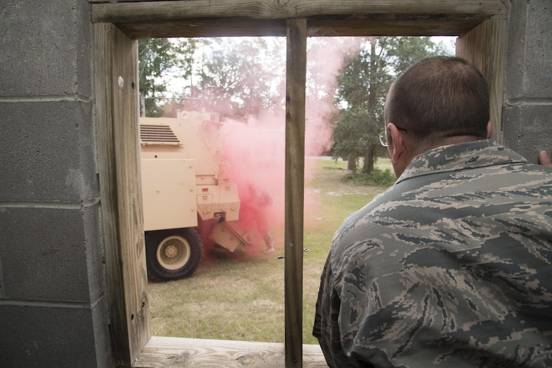Chief Master Sgt. David Wade, 9th Air Force command chief, watches Airmen from the 823rd Base Defense Squadron enter a mine-resistant, ambush protected vehicle in the cover of smoke, July 11, 2017, at Moody Air Force Base, Ga.  Wade visited the 93d Air Ground Operations Wing and its units at Moody to learn about the units' missions and capabilities. (U.S. Air Force photo by Staff Sgt. Eric Summers Jr.)