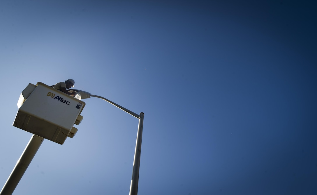 Senior Airman Darren Pizarro, 27th Special Operations Civil Engineer Squadron electrical systems specialist, replaces a faulty bulb in a light pole at Cannon Air Force Base, N.M., June 27, 2017. Specialists such as Pizarro are responsible for installing, repairing and maintaining electrical networks, ensuring that primary sources of energy are always available. From space command communicating with satellites to hospitals operating lifesaving equipment, every Air Force function depends on this crucial service provided by these experts. (U.S. Air Force photo by Senior Airman Lane T. Plummer)