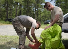 A fellow explosive ordnance disposal Airman assists Staff Sgt. Tyler Paul in donning a chemical suit in preparation to respond to a simulated chemical dispersal unit background during a three-day, multi-agency emergency response exercise at Joint Base McGuire-Dix-Lakehurst, New Jersey, on July 12, 2017. More than 40 members of the 87th Air Base Wing, FBI and Environmental Protection Agency took part in the exercise. Paul is assigned to the 87th Civil Engineer Squadron.