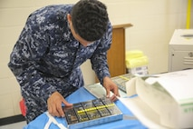 Petty Officer 3rd Class Hasmed Machuca, a dental corpsman with 4th Dental Battalion, 4th Marine Logistics Group, Marine Forces Reserve, prepares dental extraction equipment for sterilization during Innovative Readiness Training Louisiana Care 2017 at East St. John High School in Reserve, La., July 12, 2017. The Louisiana Care IRT event is a joint service medical mission that provides service members the opportunity to increase public awareness and understanding of the Marine Corps and Navy while increasing overall training and readiness. (Photo by U.S. Marine Corps Pvt. Samantha Schwoch/Released)