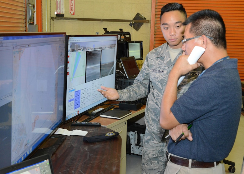 Staff Sgt. Alexander Deguzman, 412th Security Forces Squadron installation security technician, shows Bobby Truong, 412th Communications Squadron, the monitors and controls of the Raptor surveillance system that was demonstrated to base leadership July 10. (U.S. Air Force photo by Kenji Thuloweit)