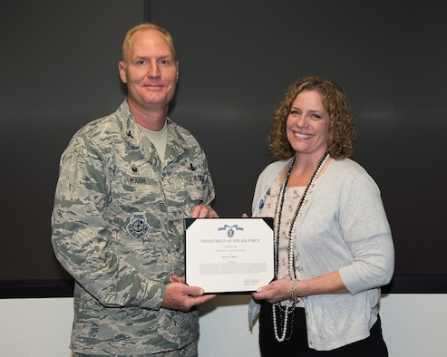 Col. Michael Hough, 30th Space Wing commander, presents Ms. Shawn Riem, 30th SW historian, with a civilian achievement award, July 12, 2017, Vandenberg Air Force Base, Calif. Riem was recognized for her distinguished performance as historian for Headquarters United States Air Forces Central Command, Al Udeid Air Base, Qatar, from Oct 2016 - Feb 2017. (U.S. Air Force photo by Michael Peterson/released)