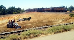 A Union Pacific train passes as the contractor works on Phase 4a of the Marysville Ring Levee project on July 7, 2017. This portion of the levee project is located in Binney Junction, adjacent to the Marysville Catholic Cemetery.