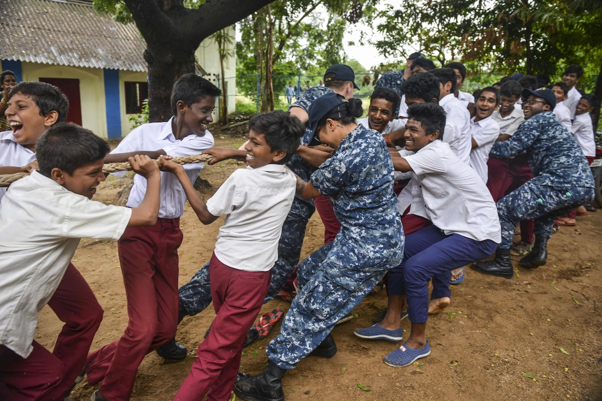 Sailors participate in a tug-of-war match with students.
