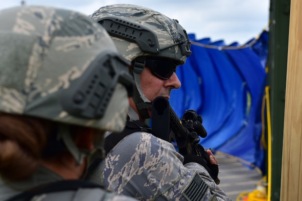 """A member of the 914th Security Forces Squadron prepares to enter a simulated building during a training exercise Wednesday, July 13, 2017, Niagara Falls Air Reserve Station, N.Y.The exercise is part of a """"shoot-move-communicate"""" annual training to test SFS members' readiness. (U.S. Air Force photo by Staff Sgt. Richard Mekkri)"""