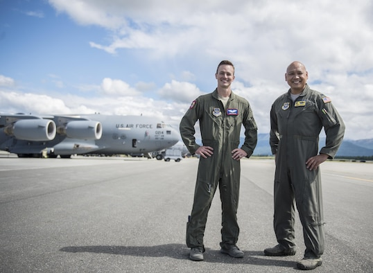 Capt. Chris Mahan (left), pilot, and Col. Jimmy Canlas (right), commander, 437th Airlift Wing pose in front of a U.S. Air Force C-17 from Joint Base Charleston, S.C., on the ramp at Joint Base Elmendorf-Richardson, Alaska, July 9, 2017 after landing to participate in and provide airlift support for Exercise Talisman Saber 2017. The purpose of TS17 is to improve U.S.-Australian combat readiness, increase interoperability, maximize combined training opportunities and conduct maritime prepositioning and logistics operations in the Pacific. TS17 also demonstrates U.S. commitment to its key ally and the overarching security framework in the Indo Asian Pacific region.