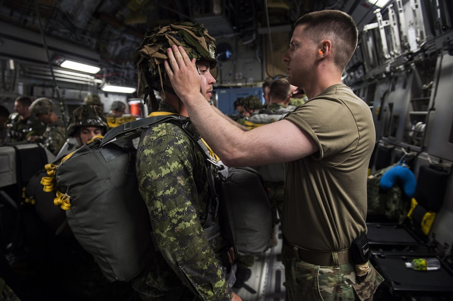 U.S. Army 1st Lt. Isaac Larue, executive officer, Alpha Company, 4th Brigade 25th Infantry division, checks the gear of a paratrooper from Princess Patricia's Canadian Light Infantry while onboard a U.S. Air Force C-17 Globemaster III from Joint Base Charleston, S.C., July 12, 2017 to conduct an air drop to participate in Exercise Talisman Saber 2017. The purpose of TS17 is to improve U.S.-Australian combat readiness, increase interoperability, maximize combined training opportunities and conduct maritime prepositioning and logistics operations in the Pacific. TS17 also demonstrates U.S. commitment to its key ally and the overarching security framework in the Indo Asian Pacific region.