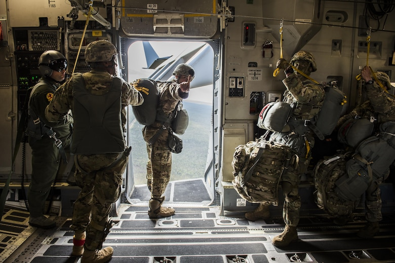 "A U.S. Army airborne jumpmaster from the 4th Brigade 25th Infantry division signals ""one minute"" to drop while he looks out of the open troop door on a U.S. Air Force C-17 Globemaster III from Joint Base Charleston, S.C., July 12, 2017 waiting to airdrop in support of Exercise Talisman Saber 2017. The purpose of TS17 is to improve U.S.-Australian combat readiness, increase interoperability, maximize combined training opportunities and conduct maritime prepositioning and logistics operations in the Pacific. TS17 also demonstrates U.S. commitment to its key ally and the overarching security framework in the Indo Asian Pacific region."