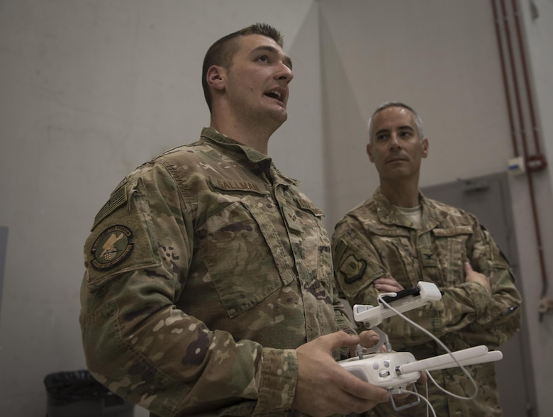 Senior Airman Christopher Gallman, 455th Expeditionary Security Forces Squadron joint defense operations center, speaks to Col. Bradford Coley, the 455th Expeditionary Mission Support Group commander, about the unmanned aircraft systems program during a live-demonstration at Bagram Airfield, Afghanistan, June 30, 2017. The 455th ESFS teamed up with a researcher from the Air Force Research Lab to teach Airmen how to pilot drones and use them to train coalition partners on how to react to them on the battlefield. (U.S. Air Force photo by Staff Sgt. Benjamin Gonsier)